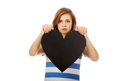 Ανησυχημένη εφηβική γυναίκα που κρατά τη μαύρη καρδιά εγγράφου Στοκ Εικόνα