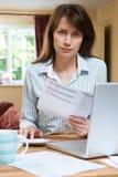 Ανησυχημένη μέση ηλικίας γυναίκα που φαίνεται στο σπίτι πόροι χρηματοδότησης Στοκ Εικόνες