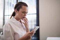 Ανησυχημένη νέα θηλυκή αποστολή κειμενικών μηνυμάτων θεραπόντων από το κινητό τηλέφωνο Στοκ εικόνα με δικαίωμα ελεύθερης χρήσης