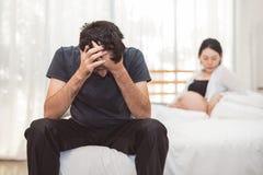 Ανησυχημένη συνεδρίαση ανδρών πίεσης στο κρεβάτι με το χέρι στο μέτωπο στην κρεβατοκάμαρα στη σοβαρή συγκίνηση διάθεσης με το έγκ στοκ εικόνες