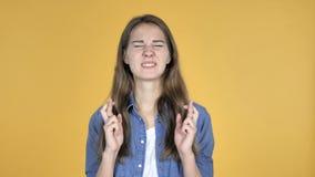Ανησυχημένη όμορφη γυναίκα που στέκεται με το δάχτυλο που διασχίζεται για την καλή τύχη στο κίτρινο υπόβαθρο απόθεμα βίντεο