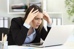 Ανησυχημένος ανώτερος υπάλληλος που λαμβάνει τις κακές ειδήσεις σε απευθείας σύνδεση στο γραφείο Στοκ Φωτογραφία