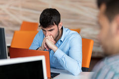 Ανησυχημένος επιχειρηματίας που εργάζεται στο γραφείο του στο γραφείο του Στοκ Εικόνες