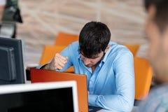 Ανησυχημένος επιχειρηματίας που εργάζεται στο γραφείο του στο γραφείο του Στοκ φωτογραφία με δικαίωμα ελεύθερης χρήσης