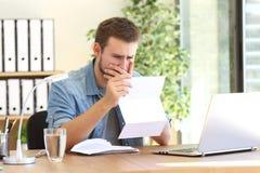 Ανησυχημένος επιχειρηματίας που διαβάζει μια επιστολή Στοκ εικόνες με δικαίωμα ελεύθερης χρήσης