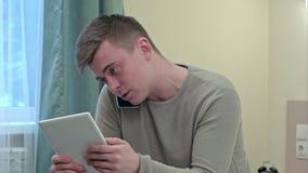 Ανησυχημένος επιχειρηματίας στα περιστασιακά ενδύματα που διαβάζει τις ειδήσεις κρεβατιών χρησιμοποιώντας την ψηφιακή ταμπλέτα το απόθεμα βίντεο
