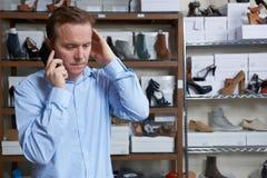 Ανησυχημένος ιδιοκτήτης του καταστήματος ακτών στο τηλέφωνο Στοκ Εικόνα