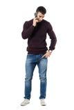 Ανησυχημένος νεαρός άνδρας στο τηλέφωνο που κοιτάζει κάτω Στοκ Εικόνες