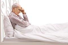 Ανησυχημένος πρεσβύτερος που βρίσκεται στο κρεβάτι Στοκ Φωτογραφία