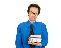 Ανησυχημένος τονισμένος δυστυχισμένος σπουδαστής με τα μεγάλα μαύρα γυαλιά που στέκονται τα βιβλία εκμετάλλευσης στοκ φωτογραφία