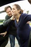 Ανησυχημένο άτομο που βοηθά τη σύζυγο με τις συστολές που εισάγονται στο αυτοκίνητο Στοκ Εικόνα