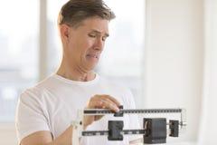 Ανησυχημένο άτομο που χρησιμοποιεί την κλίμακα βάρους στη γυμναστική Στοκ εικόνα με δικαίωμα ελεύθερης χρήσης