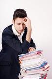 Ανησυχημένο επιχειρησιακό άτομο με πολλή γραφική εργασία. Στοκ Εικόνα