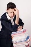Ανησυχημένο επιχειρησιακό άτομο με πολλή γραφική εργασία. Στοκ Εικόνες