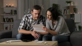 Ανησυχημένο ζεύγος που διαβάζει μια επιστολή στο σπίτι απόθεμα βίντεο
