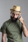 Ανησυχημένο σκεπτόμενο γενειοφόρο άτομο που φορά το καπέλο αχύρου που φαίνεται κάτω και γρατσουνίζοντας χέρι με το δάχτυλο Στοκ φωτογραφία με δικαίωμα ελεύθερης χρήσης