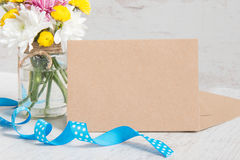 Ανθίζει την ανθοδέσμη σε ένα βάζο βάζων με τη σημείωση καρτών, το φάκελο και την μπλε κορδέλλα σε ένα άσπρο ξύλινο αγροτικό υπόβα Στοκ Φωτογραφίες