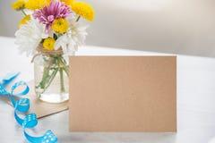 Ανθίζει την ανθοδέσμη σε ένα βάζο βάζων με τη σημείωση καρτών, το φάκελο και την μπλε κορδέλλα σε ένα άσπρο ξύλινο αγροτικό υπόβα Στοκ Εικόνες