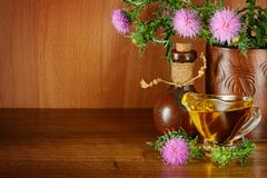 Ανθίζοντας κάρδος γάλακτος φυτών και γυαλί πετρελαίου Θεραπεία του χορταριού στο ξύλο Στοκ Εικόνες