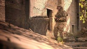 Ανθεκτικός καυκάσιος στρατιωτικός στην κάλυψη που στέκεται το ψυχρό κοντινό εγκαταλειμμένο κτήριο τούβλου, αυτόματο πυροβόλο όπλο απόθεμα βίντεο