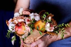 Ανθοδέσμη από τα λουλούδια και φρούτα στα χέρια η σύνθεση κεριών φθινοπώρου μήλων ξηρά βγάζει φύλλα vase απόλυσης Στοκ εικόνα με δικαίωμα ελεύθερης χρήσης