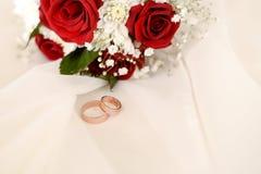 Ανθοδέσμη γαμήλιας έννοιας των κόκκινων τριαντάφυλλων και των γαμήλιων χρυσών δαχτυλιδιών στο ελαφρύ υπόβαθρο κρητιδογραφιών r στοκ φωτογραφίες