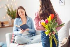 Ανθοδέσμη εκμετάλλευσης κορών ημέρας μητέρων και μητέρων ` s κορών στο σπίτι των λουλουδιών πίσω από την πίσω έκπληξη Στοκ Φωτογραφίες
