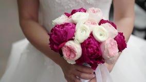 Ανθοδέσμη εκμετάλλευσης νυφών των άσπρων, ρόδινων και κόκκινων τριαντάφυλλων Κυματίζοντας κορδέλλες Υπαίθρια σε αργή κίνηση απόθεμα βίντεο
