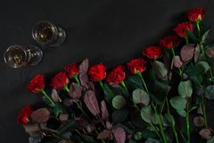 Ανθοδέσμη κόκκινων τριαντάφυλλων και δύο ποτηριών της σαμπάνιας σε μια μαύρη ΤΣΕ Στοκ Εικόνα