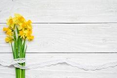 Ανθοδέσμη λουλουδιών άνοιξη των κίτρινων λουλουδιών ναρκίσσων πέρα από τον άσπρο ξύλινο πίνακα Στοκ Φωτογραφία