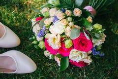 Ανθοδέσμη με τα παπούτσια που βρίσκονται δίπλα στη χλόη στοκ φωτογραφία με δικαίωμα ελεύθερης χρήσης