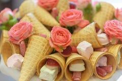 Ανθοδέσμη που αποτελείται από τα λουλούδια των τριαντάφυλλων, των κώνων βαφλών, των γλυκών και marshmallows κοντά επάνω Στοκ Εικόνα