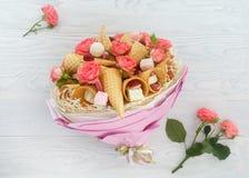 Ανθοδέσμη που αποτελείται από τα λουλούδια των τριαντάφυλλων, των κώνων βαφλών, των γλυκών και marshmallows σε ένα ελαφρύ ξύλινο  Στοκ Εικόνες