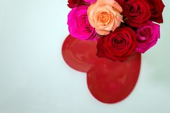 Ανθοδέσμη των κόκκινων και ρόδινων τριαντάφυλλων πέρα από την κόκκινη καρδιά Στοκ φωτογραφία με δικαίωμα ελεύθερης χρήσης