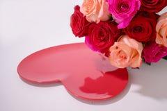 Ανθοδέσμη των κόκκινων και ρόδινων τριαντάφυλλων πέρα από την κόκκινη καρδιά στοκ φωτογραφία