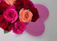 Ανθοδέσμη των κόκκινων και ρόδινων τριαντάφυλλων και του ρόδινου πιάτου καρδιών στοκ εικόνες με δικαίωμα ελεύθερης χρήσης