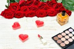 Ανθοδέσμη των κόκκινων τριαντάφυλλων, διαμορφωμένα καρδιά κεριά, άρωμα, κραγιόν Στοκ φωτογραφία με δικαίωμα ελεύθερης χρήσης
