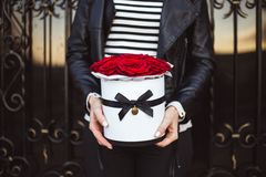 Ανθοδέσμη των κόκκινων τριαντάφυλλων σε ένα κιβώτιο στα χέρια ενός κοριτσιού στοκ φωτογραφίες με δικαίωμα ελεύθερης χρήσης