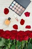 Ανθοδέσμη των κόκκινων τριαντάφυλλων, της παλέτας αρώματος, κραγιόν και σκιάς ματιών επάνω Στοκ φωτογραφία με δικαίωμα ελεύθερης χρήσης