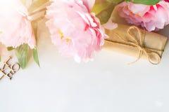 Ανθοδέσμη των λουλουδιών, κιβώτιο δώρων που τυλίγεται με το έγγραφο τεχνών, κορδέλλα για το άσπρο υπόβαθρο με το διάστημα αντιγρά στοκ εικόνα