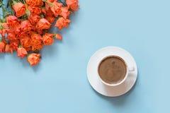 Ανθοδέσμη των πορτοκαλιών τριαντάφυλλων θάμνων και φλυτζάνι του μαύρου καφέ στο μπλε υπόβαθρο κρητιδογραφιών Επίπεδος βάλτε διάστ Στοκ εικόνες με δικαίωμα ελεύθερης χρήσης