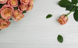 Ανθοδέσμη των ροδαλών λουλουδιών στο ξύλινο πρότυπο επιτραπέζιων ευχετήριων καρτών στοκ φωτογραφία με δικαίωμα ελεύθερης χρήσης