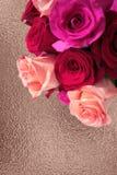 Ανθοδέσμη των ρόδινων και κόκκινων τριαντάφυλλων στο ροδαλό χρυσό υπόβαθρο στοκ φωτογραφίες