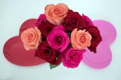 Ανθοδέσμη των τριαντάφυλλων μεταξύ δύο διαμορφωμένων καρδιά πιάτων στοκ εικόνα με δικαίωμα ελεύθερης χρήσης