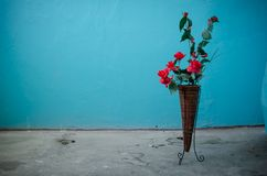 Ανθοδέσμη των φωτεινών ρόδινων τεχνητών τριαντάφυλλων στη στάση στα πλαίσια του τυρκουάζ τοίχου στην είσοδο Άκρες τσιγάρων στοκ φωτογραφία