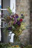 Ανθοδέσμη φιαγμένη επάνω από anemones, τριαντάφυλλα και hydrangeas, σε ένα βάζο για την πώληση σε έναν μετρητή σε ένα ανθοπωλείο Στοκ Φωτογραφίες