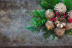 Ανθοδέσμη Χριστουγέννων με τους χρυσούς κώνους πεύκων, κόκκινα μούρα και αειθαλής στο ξύλινο υπόβαθρο στοκ φωτογραφίες