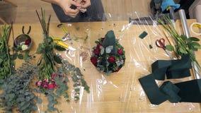 Ανθοκόμος άποψης άνωθεν που εργάζεται με τη floral σύνθεση στον πίνακα απόθεμα βίντεο