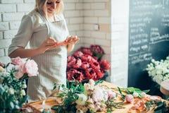 Ανθοκόμος γυναικών που παίρνει τις εικόνες των λουλουδιών με το κινητό τηλέφωνο στοκ φωτογραφία με δικαίωμα ελεύθερης χρήσης