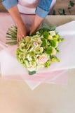 Ανθοκόμος που τακτοποιεί τα όμορφα λουλούδια στο έγγραφο τεχνών Στοκ Εικόνες